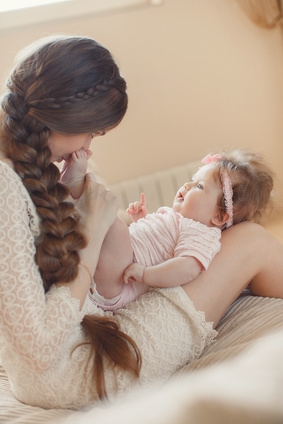 Happy mother playing with child at home